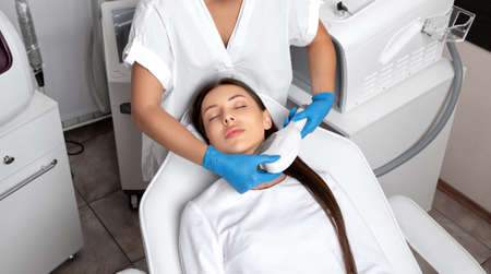 Elos epilation hair removal procedure on the face of a woman. Beautician doing laser rejuvenation on the neck in a beauty salon. Facial skin care. Hardware ipl cosmetology
