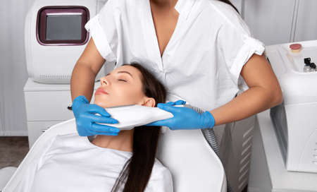 Elos epilation hair removal procedure on the face of a woman. Beautician doing laser rejuvenation on the chin in a beauty salon. Facial skin care. Hardware ipl cosmetology