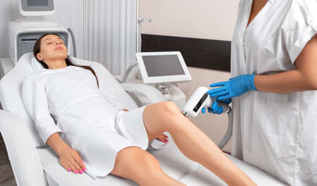 Elos epilation hair removal procedure on a woman's body. Beautician doing laser rejuvenation on the lower leg in a beauty salon. Removing unwanted body hair. Hardware ipl cosmetology Archivio Fotografico - 150719938