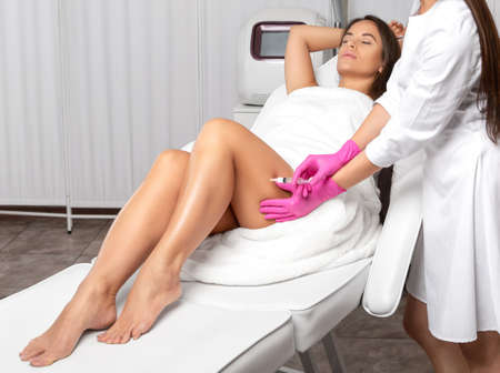 Aesthetic cosmetologist makes lipolytic injections to burn fat on the thighs, hips and body of a woman. Female aesthetic cosmetology in a beauty salon.Cosmetology concept.