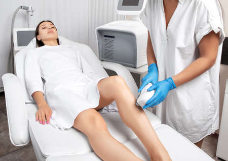 Elos epilation hair removal procedure on a woman's body. Beautician doing laser rejuvenation on the lower leg in a beauty salon. Removing unwanted body hair. Hardware ipl cosmetology Stock Photo