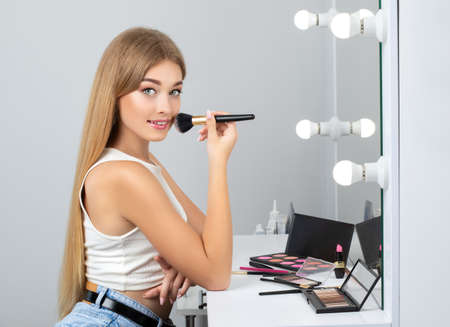 Beautiful young blonde with clean fresh skin, long blond hair holds brush in her hands and does makeup in front of a mirror with lamps.Near her there are many eye shadow and face powder.Make-up concept