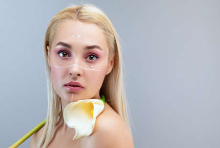 Portrait of a beautiful happy woman with long eyelashes, beautiful creative make-up, thick eyebrows and with clean skin in. She holds calla flowers near her face. Makeup and cosmetology skin care. Archivio Fotografico - 152066144