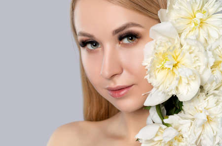 Portrait of a beautiful blonde woman with long hair, beautiful fresh makeup and healthy clean skin with peonies in her hands. Makeup and cosmetology concept. Imagens