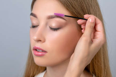 Make-up artist combing eyebrows with a brush to a beautiful young blonde teen girl with long hair, makeup, clean skin after permanent makeup. Makeup concept, eyebrow shape modeling. Archivio Fotografico