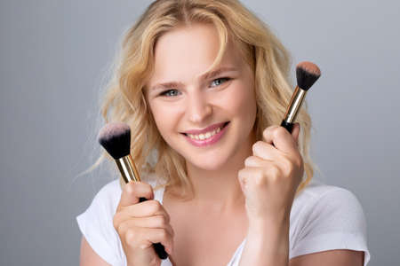 Portrait of a beautiful woman with curly blond hair, beautiful fresh makeup and healthy clean skin holding a powder brush in her hands. Professional makeup and skin care cosmetology. Archivio Fotografico - 152069447
