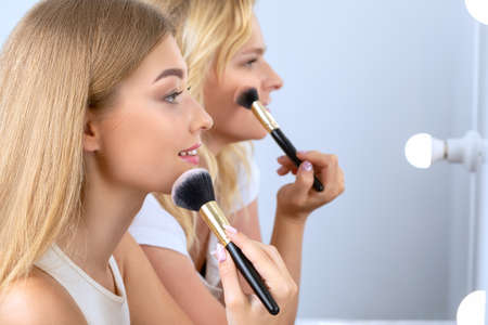 Two beautiful young blonde with clean fresh skin, long blond hair is doing makeup in front of a mirror with lamps. Professional makeup and cosmetology skin care.
