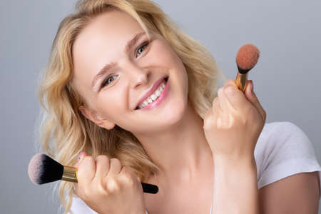 Portrait of a beautiful woman with curly blond hair, beautiful fresh makeup and healthy clean skin holding a powder brush in her hands. Professional makeup and skin care cosmetology. Archivio Fotografico - 152226123