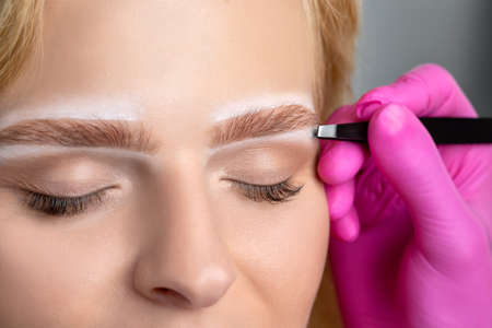 Woman having Permanent Make-up Tattoo on her Eyebrows. Eyelash artist plucks eyebrows with tweezers. Professional makeup and cosmetology skin care. Archivio Fotografico - 152226131