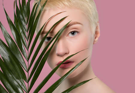 Portrait of a beautiful woman with short blonde hair, beautiful fresh make-up and with healthy clean skin with a green leaf on a pink background. Makeup and aesthetic cosmetology concept. 스톡 콘텐츠