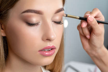 Portrait of a beautiful woman with fresh nude make-up, thick eyebrows and with clean skin. Makeup artist does eye makeupin a beauty salon. Cosmetology and Makeup concept. Archivio Fotografico - 152069455