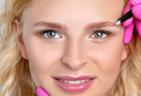 Woman having Permanent Make-up Tattoo on her Eyebrows. Eyelash artist plucks eyebrows with tweezers. Professional makeup and cosmetology skin care.