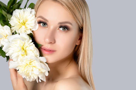 Portrait of a beautiful blonde woman with long hair, beautiful fresh makeup and healthy clean skin with peonies in her hands. Makeup and cosmetology concept. 스톡 콘텐츠