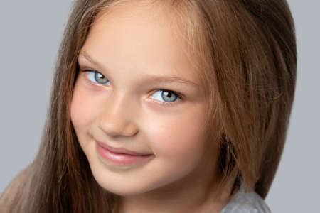 Portrait of a beautiful smiling girl with blue eyes, with light brown hair. She looks into the camera. Family concept.