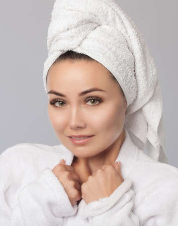 Portrait of a beautiful, smiling woman with clean skin in a white bathrobe after taking a shower. Women's cosmetology and daily skin care at home.