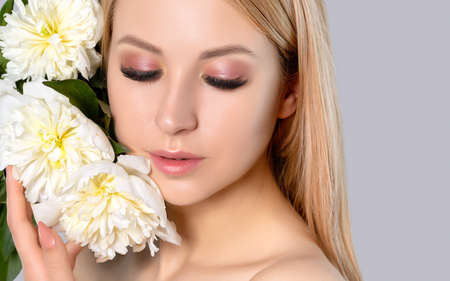 Portrait of a beautiful blonde woman with long hair, beautiful fresh makeup and healthy clean skin with peonies in her hands. Makeup and cosmetology concept. Archivio Fotografico - 152157280
