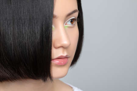 Portrait of a beautiful teenage girl with dark hair, with beautiful creative white-green makeup and healthy clean skin. Makeup and cosmetology concept. Archivio Fotografico