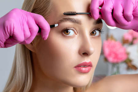 Eyelash artist plucks eyebrows with tweezers. Beautiful blonde woman having Permanent Make-up Tattoo on her Eyebrows. Professional makeup and cosmetology skin care.