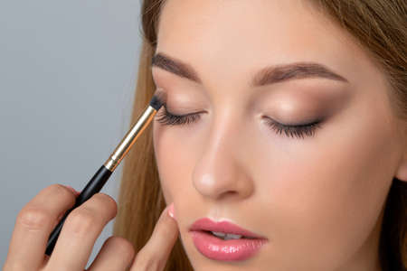 Portrait of a beautiful woman with fresh nude make-up, thick eyebrows and with clean skin. Makeup artist does eye makeupin a beauty salon. Cosmetology and Makeup concept.
