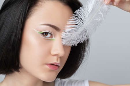Portrait of a beautiful teenage girl with dark hair, with beautiful creative white makeup and healthy clean skin. She is holding a white peacock feather near her face. Makeup and cosmetology concept. Archivio Fotografico - 152158969