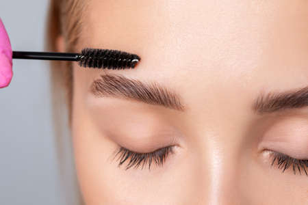 Make-up artist combing eyebrows with a brush to a beautiful young blonde woman with clean skin after permanent makeup. Makeup and cosmetology concept, eyebrow shape modeling.