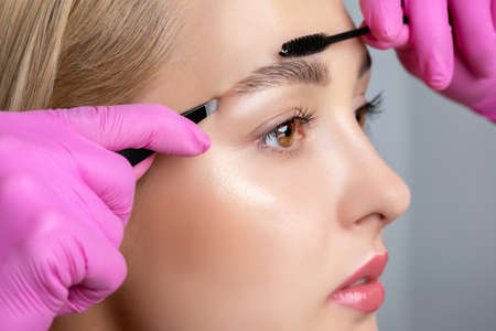 Eyelash artist plucks eyebrows with tweezers. Beautiful blonde woman having Permanent Make-up Tattoo on her Eyebrows. Professional makeup and cosmetology skin care. Archivio Fotografico - 152158979