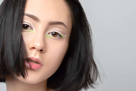 Portrait of a beautiful teenage girl with dark hair, with beautiful creative white makeup and healthy clean skin. Makeup and cosmetology concept. Archivio Fotografico