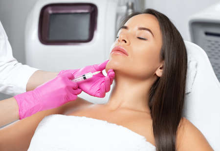 Cosmetologist makes lipolytic injections to burn fat on the chin, cheeks and neck of a woman against double chin. Female aesthetic cosmetology in a beauty salon.Cosmetology concept.