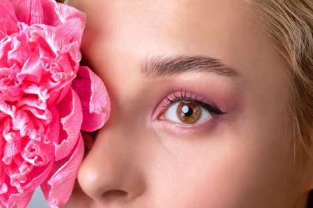 Portrait of a beautiful girl with blond hair, with beautiful creative pink makeup and healthy clean skin. There is a beautiful flower near her face. Makeup and cosmetology concept. Archivio Fotografico - 152656601