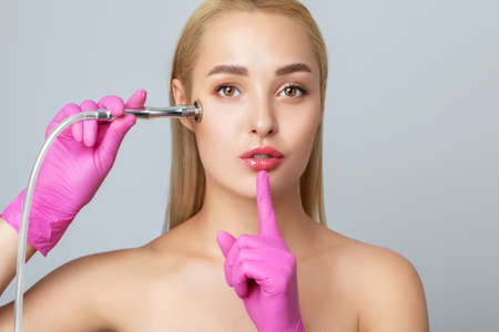 Beautiful young blonde woman with clean fresh skin naked shoulders holds a nozzle for microdermabrasion in her hands.She will do cosmetic procedure microdermabrasion.Aesthetic cosmetology.