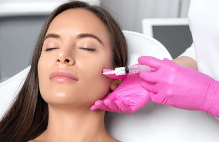 Cosmetologist makes lipolytic injections to burn fat on the chin, cheeks and neck of a woman against double chin. Female aesthetic cosmetology in a beauty salon.Cosmetology concept. Archivio Fotografico - 152499125
