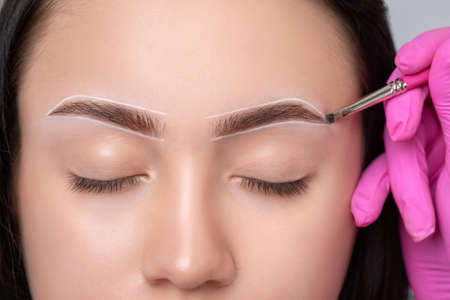 Brunette teenager girl having permanent makeup tattoo on her eyebrows. Make-up artist makes markings with white paste for eyebrow tattooing. Professional makeup and skin care cosmetology.