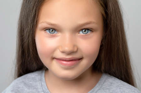 Portrait of a beautiful smiling girl with blue eyes, with light brown hair. She looks into the camera. Family concept. Archivio Fotografico - 152499031