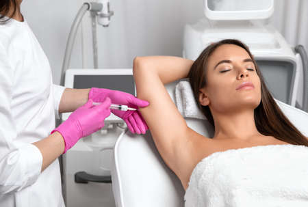 Aesthetic cosmetologist makes lipolytic injections to burn fat on the arm and body of a woman. Female aesthetic cosmetology in a beauty salon.Cosmetology concept. Archivio Fotografico - 154384504
