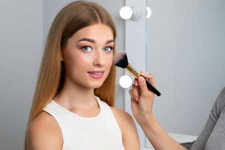 Portrait of beautiful young teenage girl with blonde hair, beautiful fresh makeup and healthy clean skin. Makeup artist holds a powder brush in her hands. Professional makeup and cosmetology skin care.