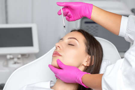 Cosmetologist makes rejuvenating anti wrinkle injections on the chin, cheeks and neck of a beautiful brunette woman. Female aesthetic cosmetology in a beauty salon.
