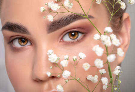 Eyes and eyebrows close up. Portrait of a beautiful teenage girl with beautiful makeup and healthy clean skin. Near the face is small white flower. Makeup and cosmetology concept. Archivio Fotografico - 154384531