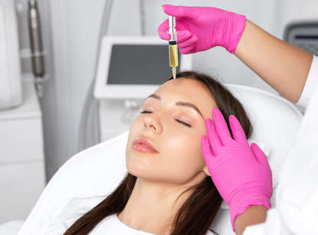 The beautician makes an anti-wrinkle PRP injections on the face to a beautiful woman at the beautician. Female aesthetic cosmetology in a beauty salon. Archivio Fotografico