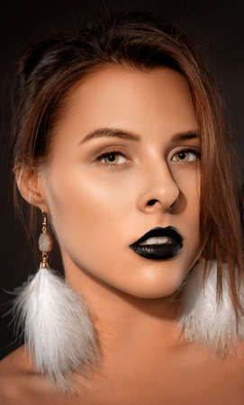 Woman with beautiful makeup and black lipstick on her lips, in the Gothic style. She has white feather earrings. Makeup and cosmetology concept. Archivio Fotografico