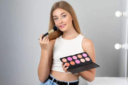 Portrait of a beautiful woman with blonde hair, beautiful fresh make-up and with healthy clean skin holds a blush and powder palette in her hands. Professional makeup and cosmetology skin care.
