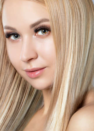 Portrait of a beautiful smiling blonde woman with naked shoulders, with blue eyes, plump lips, clean skin and fresh make-up. Aesthetic cosmetology, hair treatment and makeup concept.