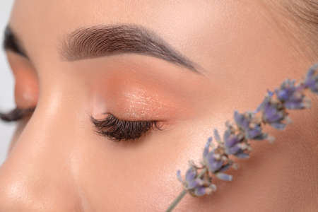 Eyes and eyebrows close-up.Portrait of a beautiful teenage girl with beautiful makeup, extended long eyelashes and healthy clean skin.Near the eyes is branch of lavender.Makeup and cosmetology concept