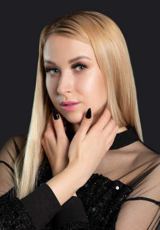Beautiful smiling blonde woman with long hair, clean skin and fresh make-up. She has beautiful blue eyes with pupil heterochromia. Aesthetic cosmetology, hair treatment and makeup concept.