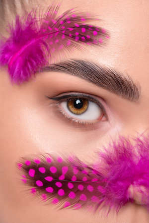 Eyes and eyebrows close-up. Portrait of a beautiful teenage girl with beautiful makeup and healthy clean skin. She is holding pink feathers near her face. Makeup and cosmetology concept. Archivio Fotografico