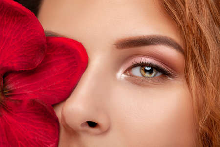 Eyes and eyebrows close up. Portrait of a beautiful teenage girl with beautiful makeup and healthy clean skin. Near the face is red orchid flower. Makeup and cosmetology concept.