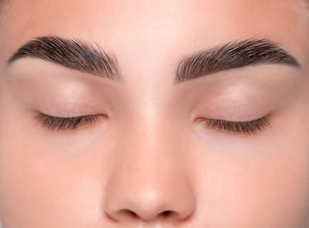 Eyebrows of a young teenager girl after plucking and cutting close-up. The make-up artist done permanent eyebrow makeup. Makeup and cosmetology concept, eyebrow shape modeling.