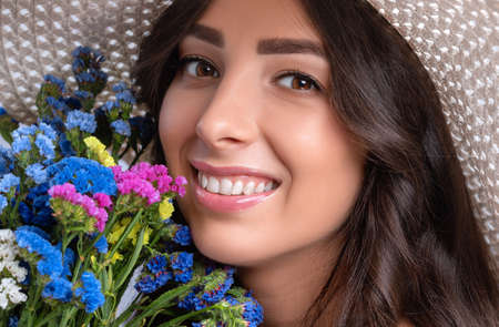 Portrait of a beautiful girl with beautiful makeup and healthy clean skin. She is wearing a light-colored hat. She holds a bouquet of colorful flowers near her face. Makeup concept. Archivio Fotografico