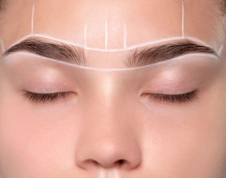 teenager girl having permanent makeup tattoo on her eyebrows. Make-up artist makes markings with white paste for eyebrow dyeing. Professional makeup and skin care cosmetology.