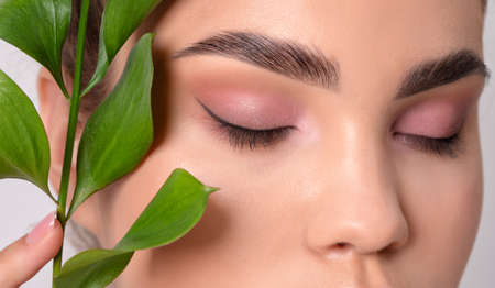 Eyes and eyebrows close up. Portrait of a teenage girl with beautiful makeup and healthy clean skin. Near the face is a branch of eucalyptus. Makeup and cosmetology concept.