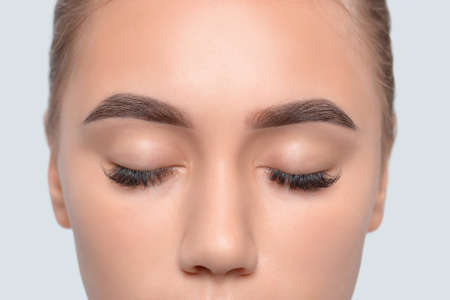 Eyebrows of a young teenager girl after plucking and cutting close-up. The make-up artist will do permanent eyebrow makeup. Makeup and cosmetology concept, eyebrow shape modeling. Archivio Fotografico